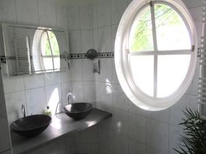 Ruime badkamer met dubbel wasbak en uiticht op de Abdij.